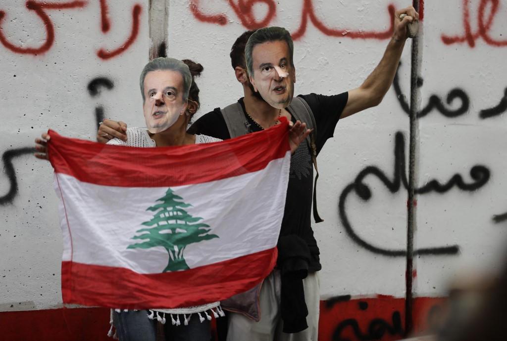 Des manifestants libanais portant des masque à l'image du gouverneur de la Banque centrale du Liban, Riad Salamé, lors d'une manifestation devant le siège de la banque à Beyrouth, le 27 novembre 2019.